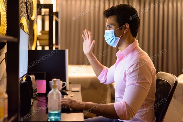 Young Indian businessman with mask video calling while working overtime at home during quarantine