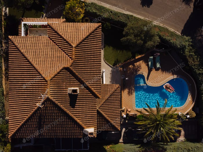 man on beach mat in swimming pool of a villa house