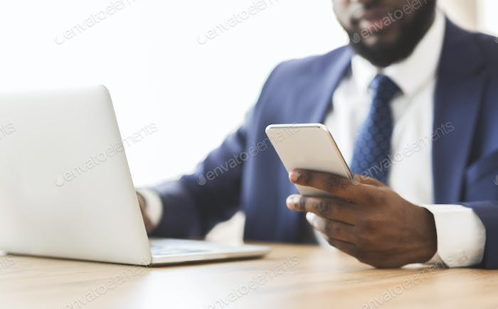 Close up of businessman using cellphone at workplace