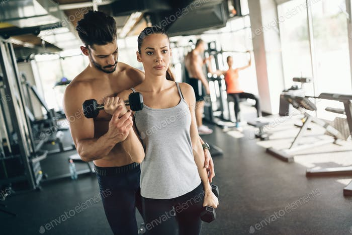 Beautiful woman helped by trainer