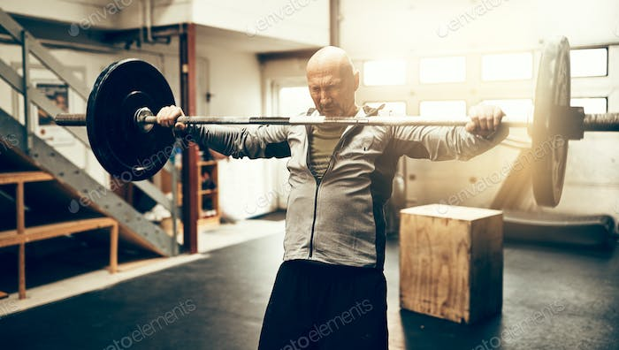 Mature man preparing to drop his barbell at the gym