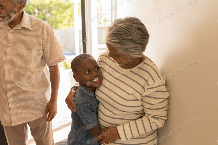 Front view of a happy African American grandmother embracing her grandson at home