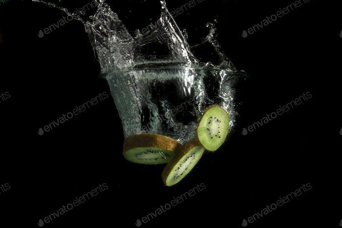 Fresh kiwi fruit slices falls in water with a big splash