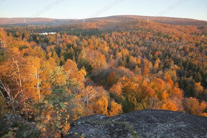 Kleiner See Umgeben von Hügeln mit Bäumen in Herbstfarbe