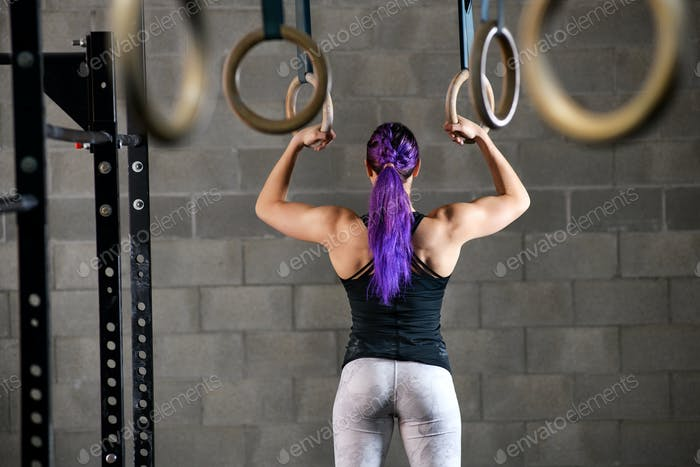 Woman athlete preparing to work out on the rings