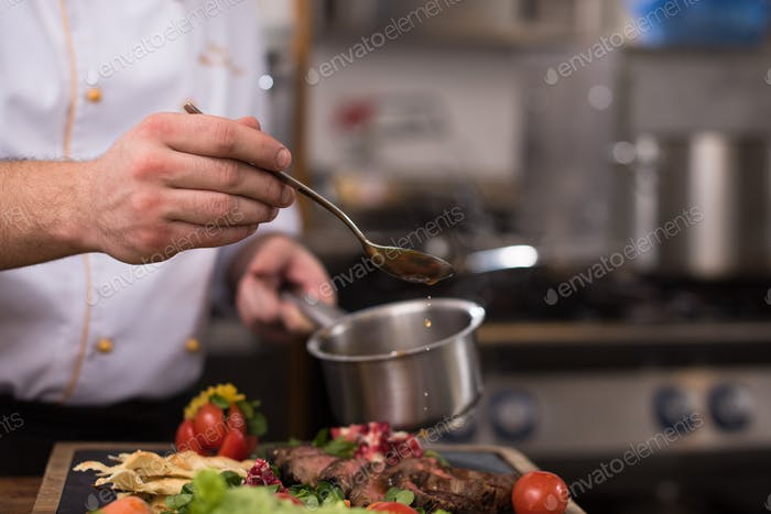 Chef hand finishing steak meat plate
