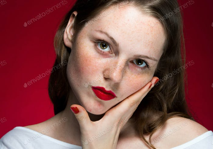 Beautiful girl portrait on red background red lips and freckles face closeup