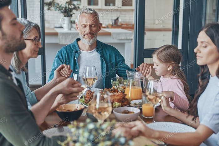 Happy multi-generation family holding hands and praying before having dinner