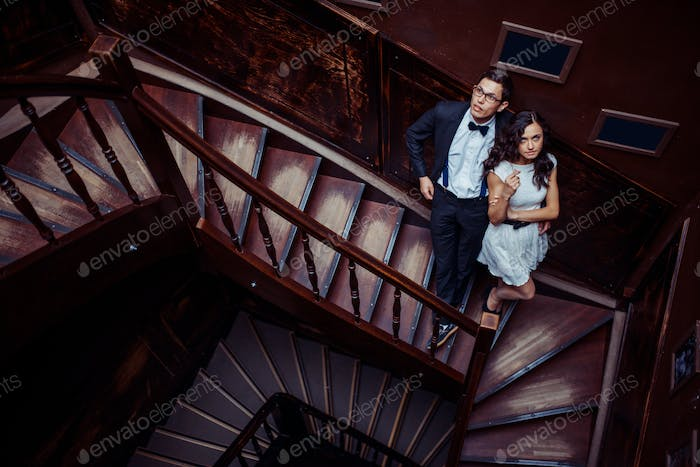 Fashionable young couple standing on stairs and hugging each other