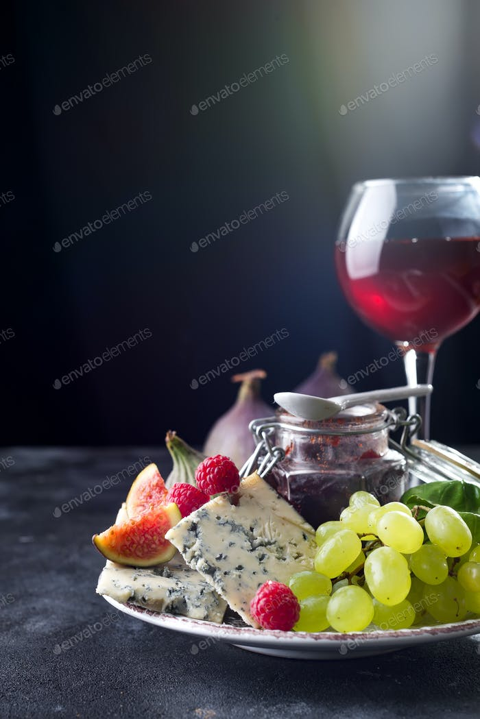 delicacy blue cheeses, fruit and jam in jar with red wine in glass