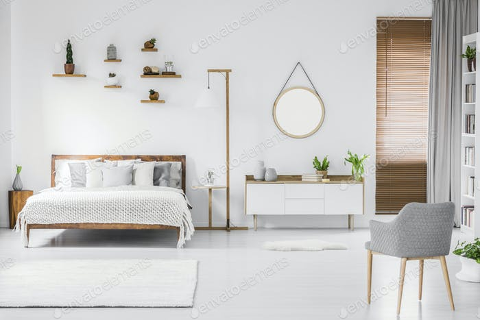 Spacious designer white bedroom interior with wooden bed with be
