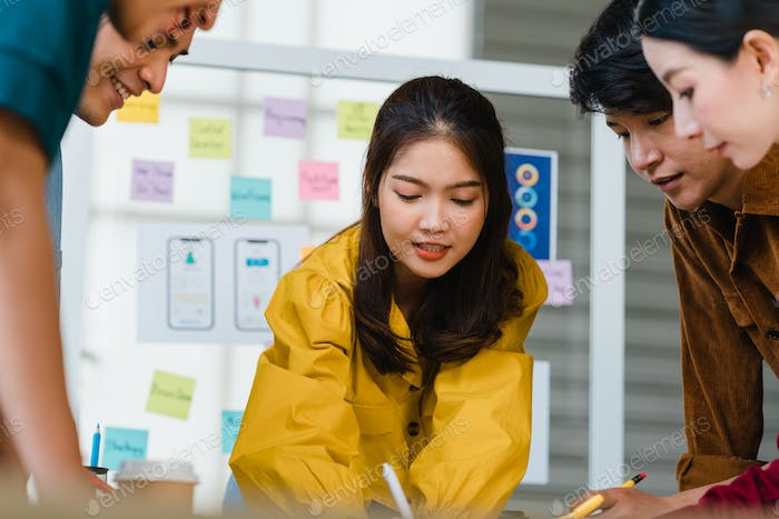 Asian businessmen and businesswomen meeting brainstorming working together in small office.