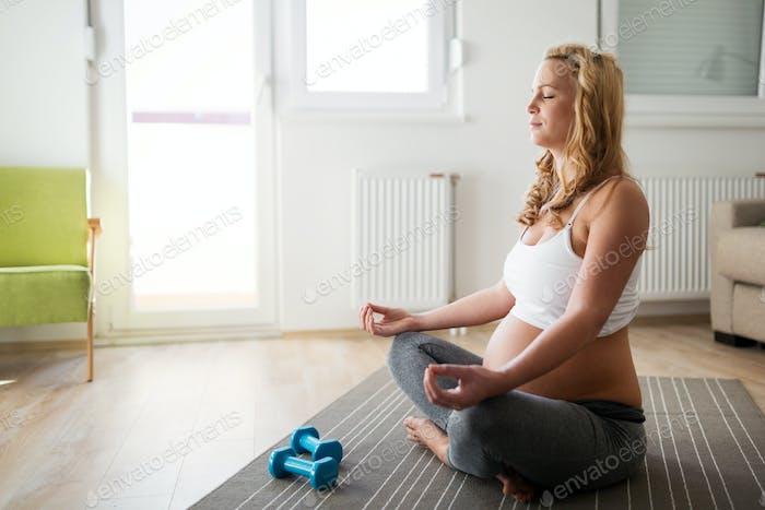Schwangere Frau entspannt und praktiziert Yoga zu Hause
