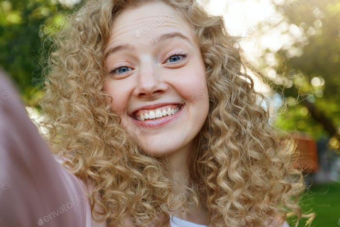 Young beautiful funny cool girl blonde with curly hair, widely smiling