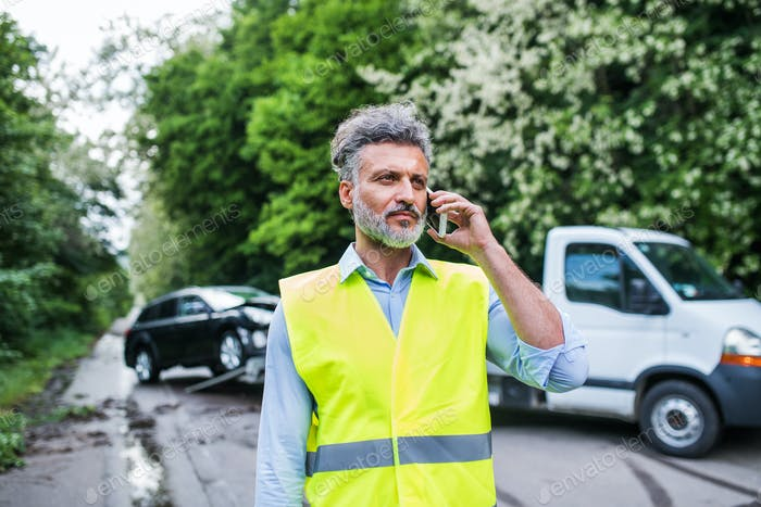 Mature man making a phone call after a car accident. Copy space.