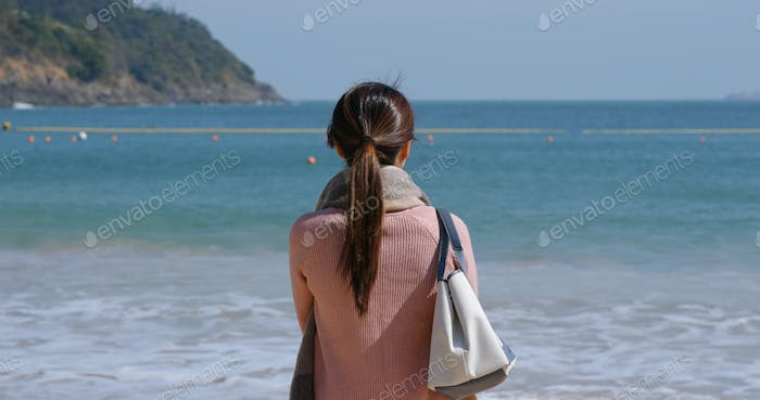 Woman looks at the sea at winter time