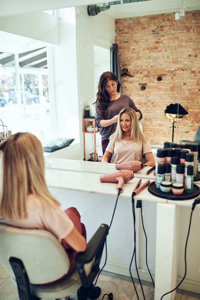 Young blonde women smiling during a hair salon appointment