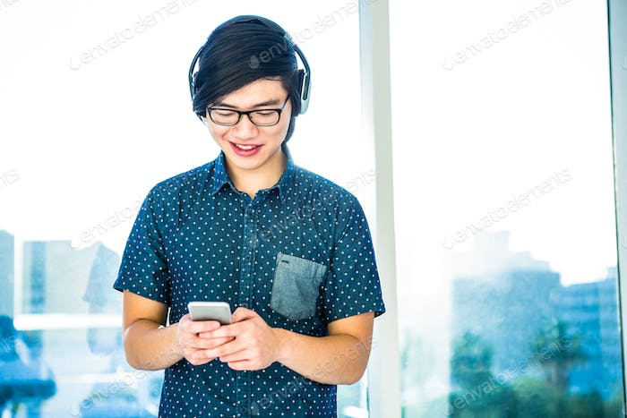 Smiling hipster businessman listening music in his office