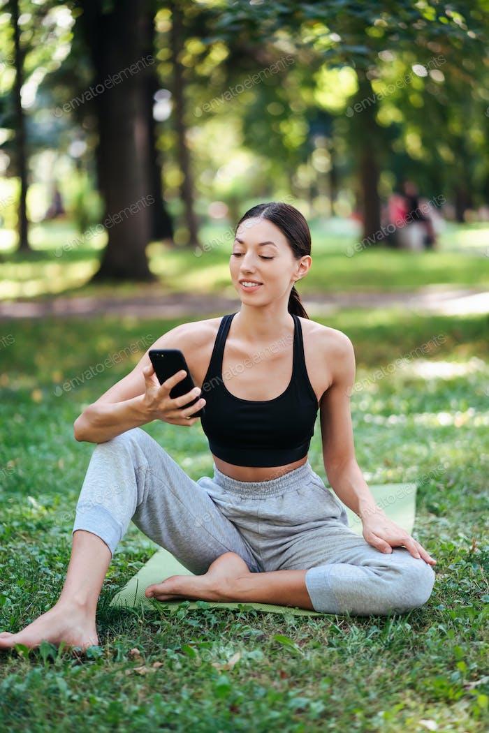 Chica de fitness con un teléfono inteligente sobre Fondo de la Naturaleza