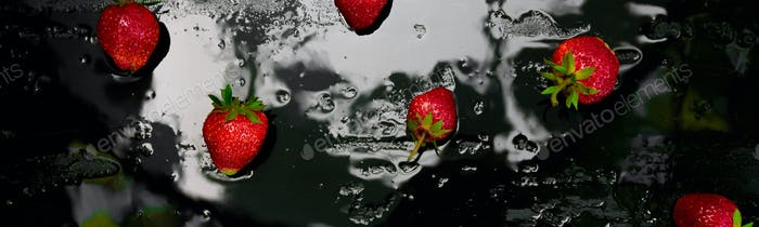 Banner of Whole strawberries on black background with water drops. Wet strawberries