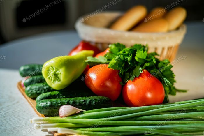 Fresh seasonal vegetables on wooden board on table