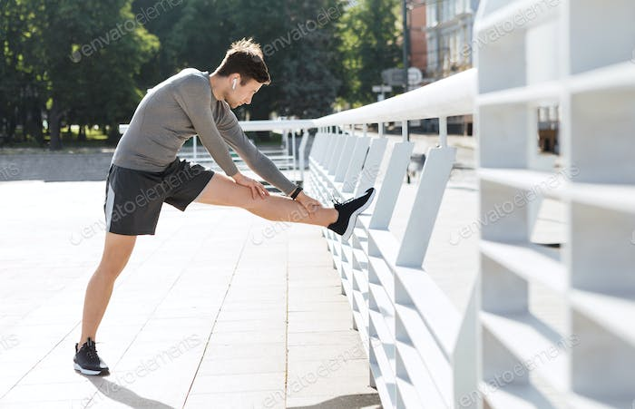 Stretching and end of workout. Muscular guy puts foot on railing and does exercises