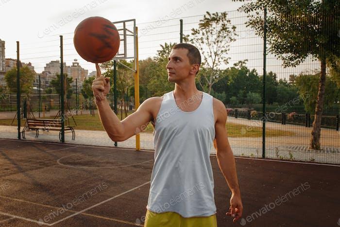 Jugador de baloncesto girando la pelota en su dedo