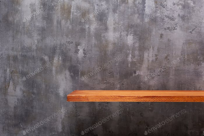 Wooden book shelf at abstract wall background, concrete or putty texture