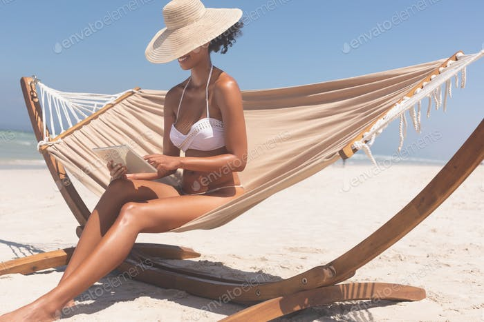 Pretty young mixed race woman in bikini with hat using digital tablet while sitting on hammock