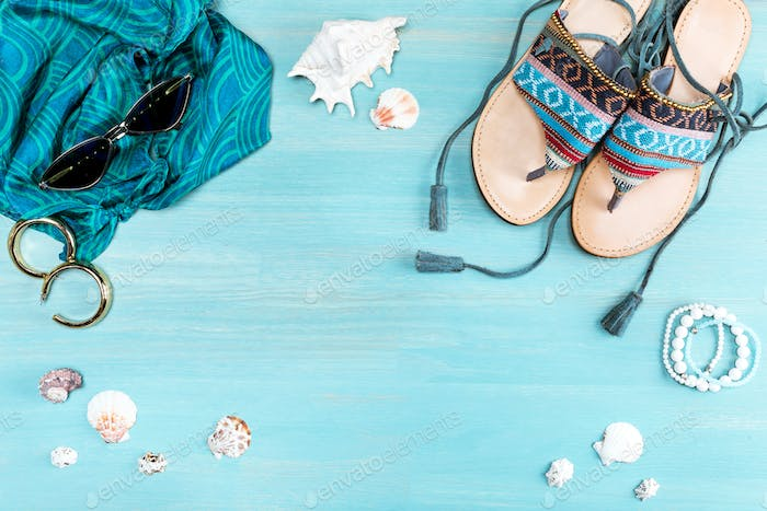 top view of sunglasses, sandals, scarf and sea shells on table