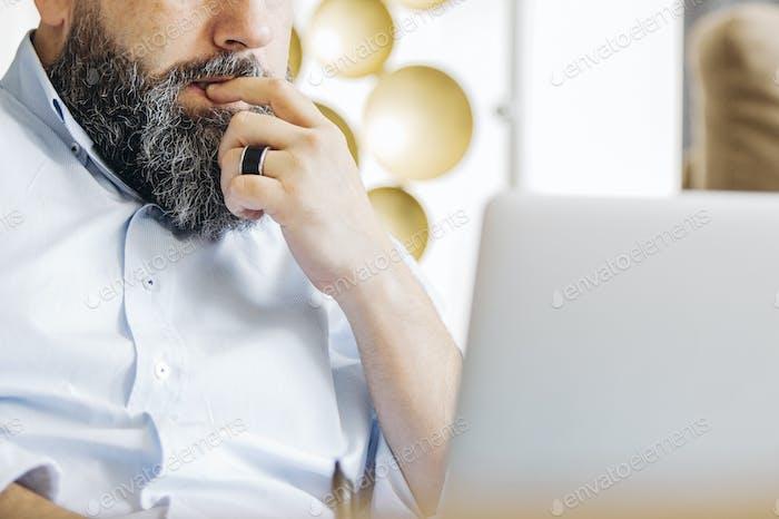 Nachdenklicher bärtiger Mann mit Laptop