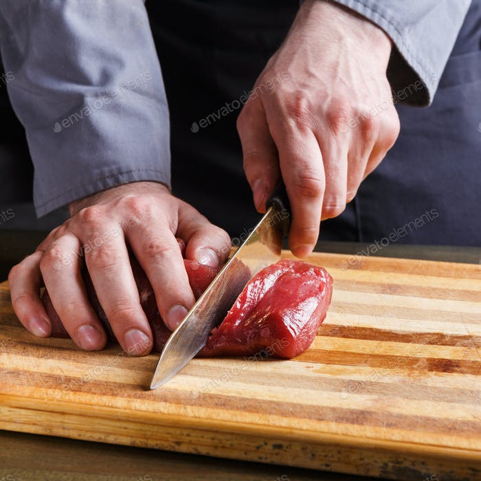 Chef cutting filet mignon on wooden board at restaurant kitchen