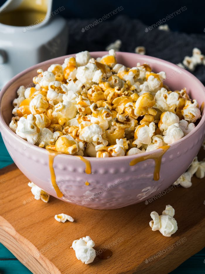 Popcorn with caramel in bowl on dark background