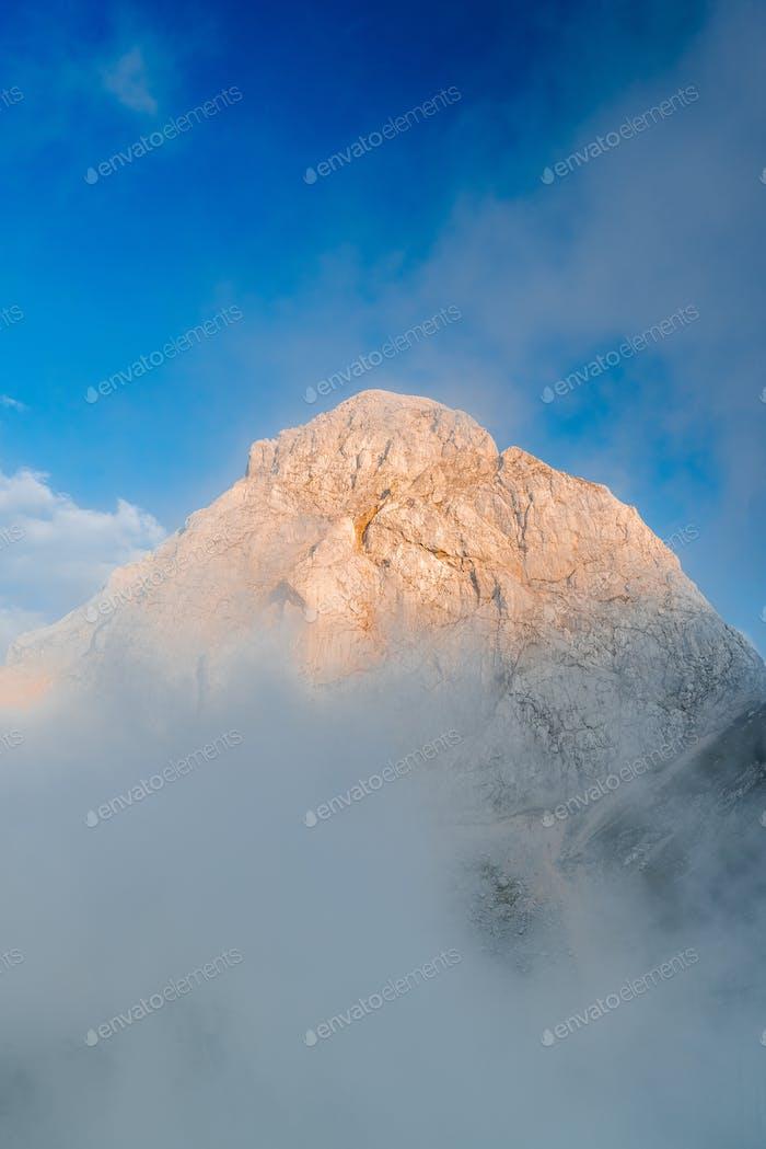 Sunset Illuminated Mangart Mountain Peak über Wolken, Slowenien