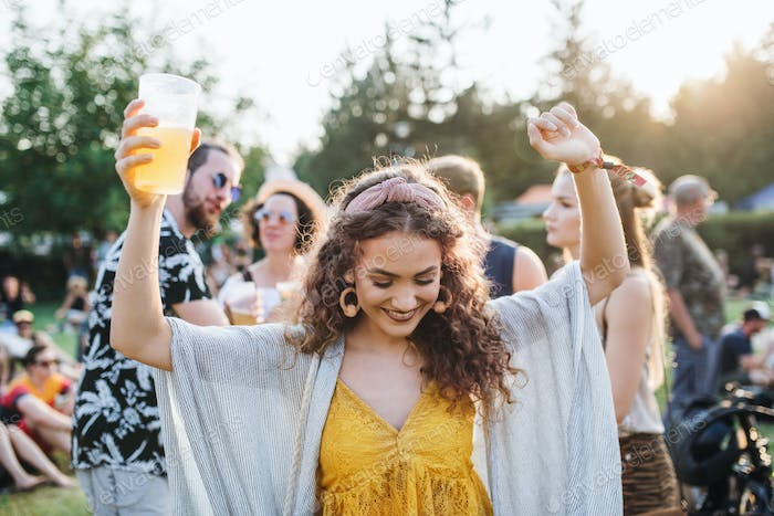 A young woman with drink dancing at summer festival
