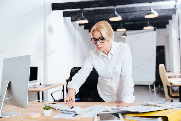 Lächelnde Geschäftsfrau stehen und schauen auf Computer diplay