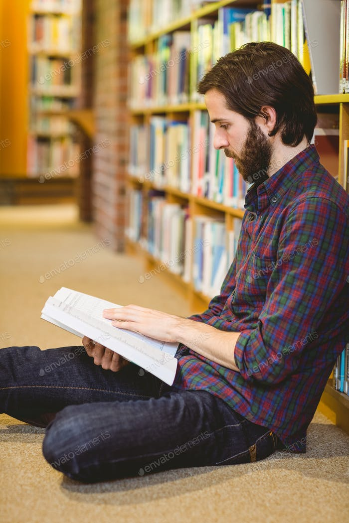 Student reading book in library on floor at the university