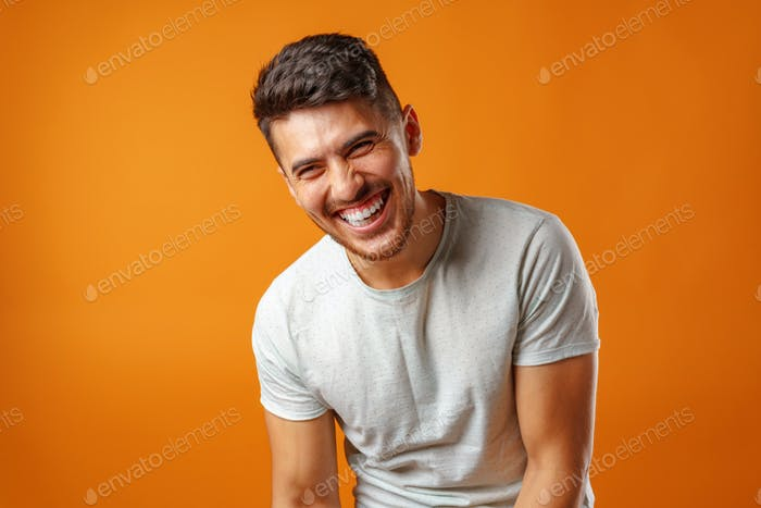 Young positive european man standing in blank white shirt laughing
