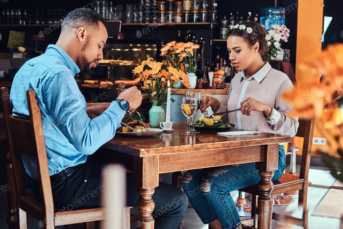 Happy beautiful African-American couple in love having a great time together in a restaurant