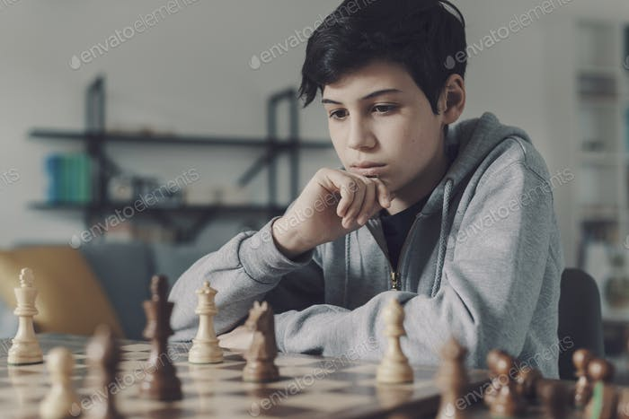 Focused boy playing chess at home