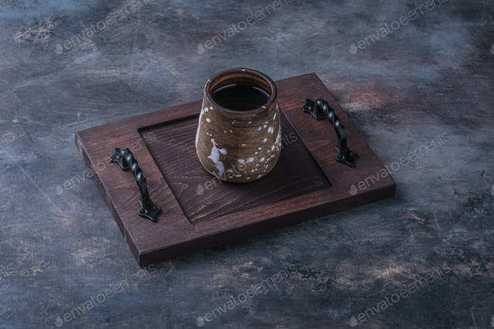 Handmade cup with coffee on wooden board, dark photo