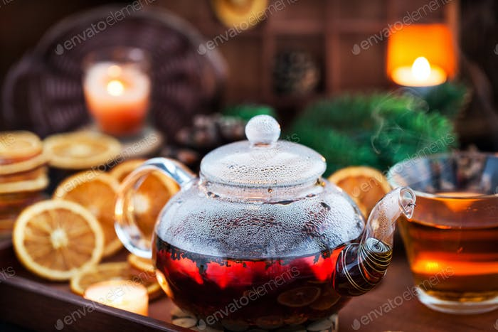 Glass teapot of hot black tea on cozy background with dried oran