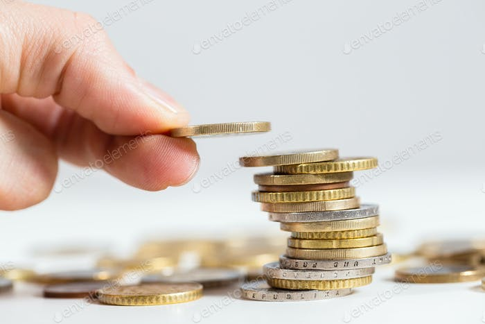 Fingers holding coin over the stack of money from close up