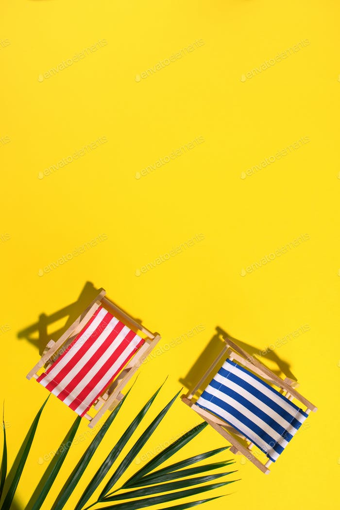 Deck chair with hard shadow, palm leaves on yellow paper background. Flat lay and copy space. Summer