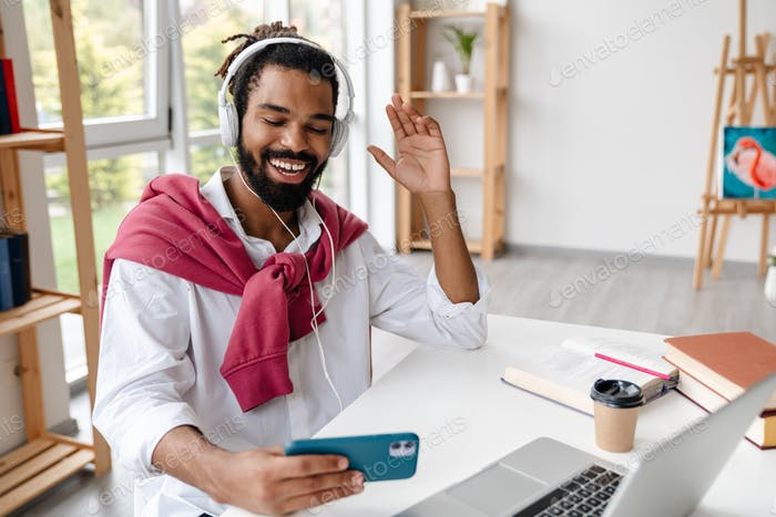 Happy african american guy in headphone using cellphone and waving hand