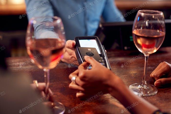 Nahaufnahme der Frau zahlen für Getränke an der Bar nach der Arbeit mit kontaktlosen Karte
