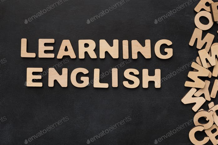 Learning English spelled with wooden letters on black background