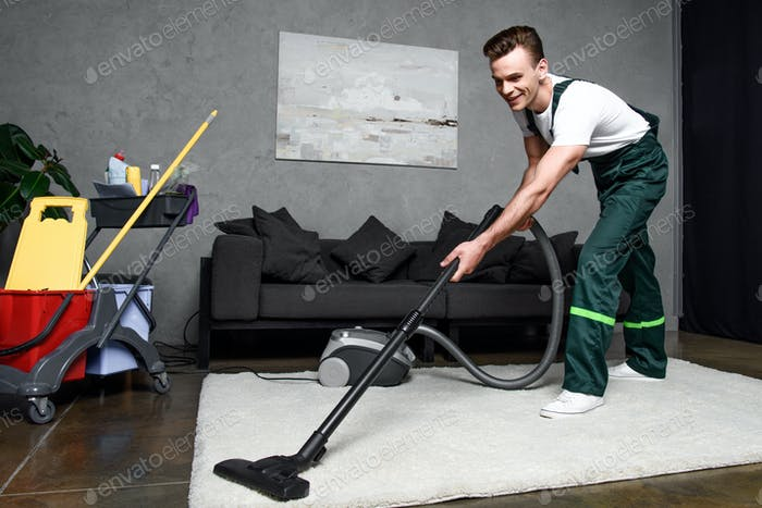 smiling young professional cleaner cleaning carpet with vacuum cleaner
