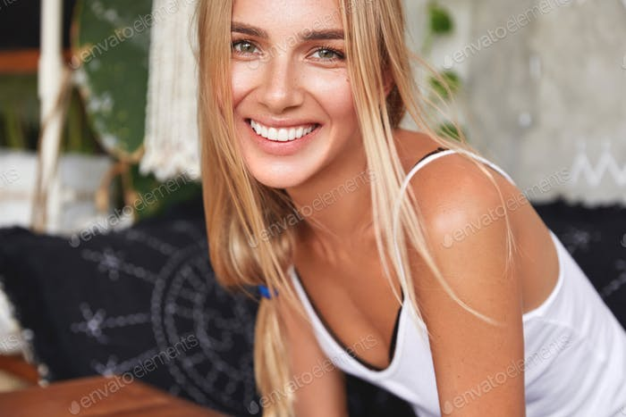 Cute smiling young woman with attractive look, has broad smile as laughs joyfully, hears positive ne