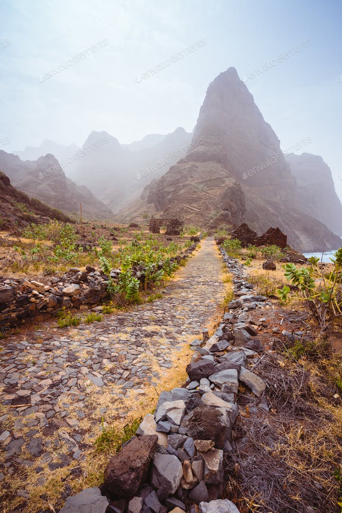 Cobbled hiking path to Ponta do Sol over amazing arid Aranhas valley with huge mountain peak and